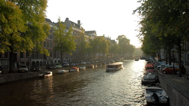 t/l, ws, boats on canal at sunset, amsterdam, north holland, netherlands - amsterdam stock videos & royalty-free footage