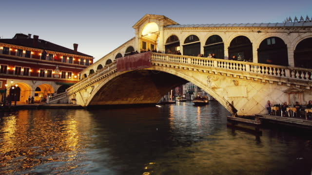 T/L, MS, Boats on Grand Canal floating under Rialto Bridge, day to dusk, Venice, Italy