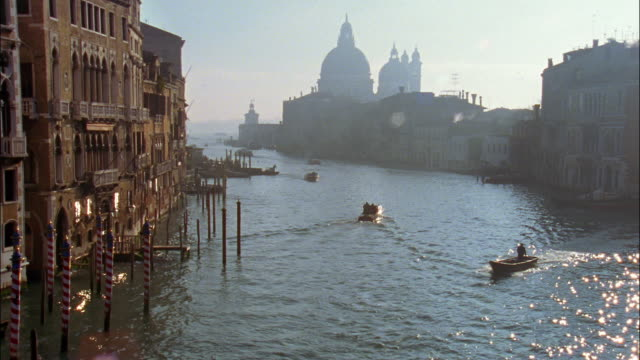 Boats on Grand Canal move toward and away from the silhouetted Santa Maria della Salute church in Venice, Italy.