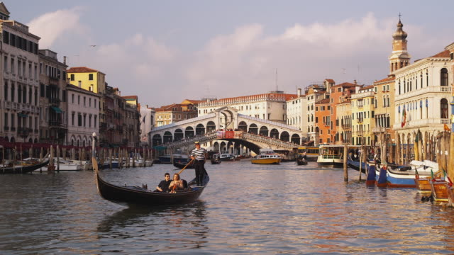 ws, boats on grand canal, rialto bridge in background, venice, italy - venice stock videos and b-roll footage