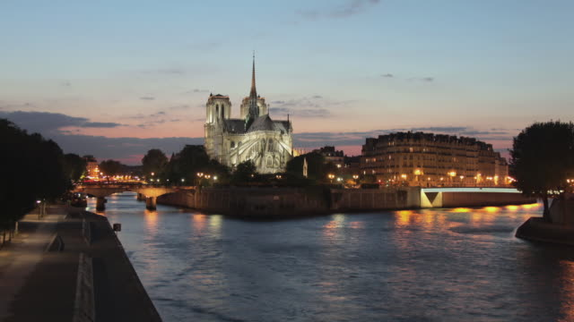 T/L WS HA Boats on river Seine with Notre Dame cathedral in background, dusk to night / Paris, Ile de France, France