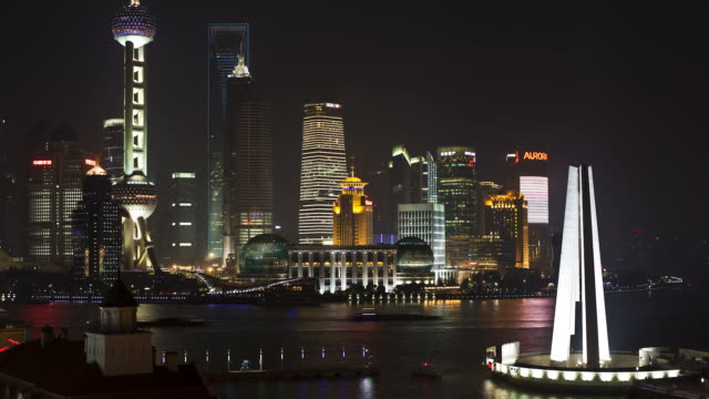 Boats on the Huangpu River pass the illuminate skyscrapers in the Pudong skyline.