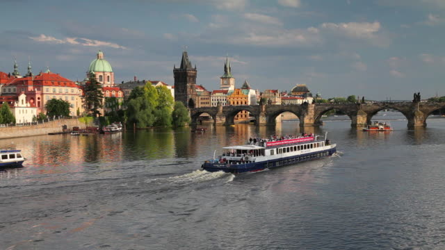 boats on the vltava river pass near the charles bridge. - hradcany castle stock videos and b-roll footage