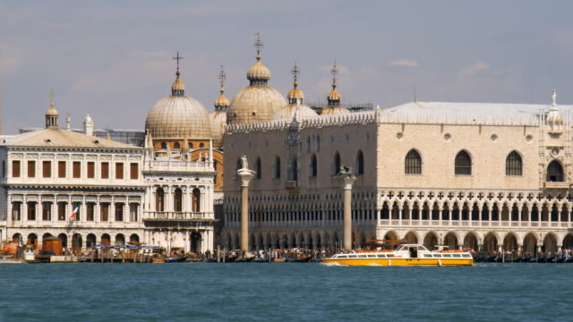 Boats pass by Doge's Palace and St. Mark's Basilica by way of the Venetian Lagoon.