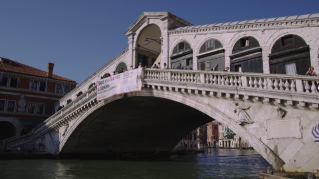 vídeos y material grabado en eventos de stock de boats pass under the rialto bridge in venice. - puente de rialto