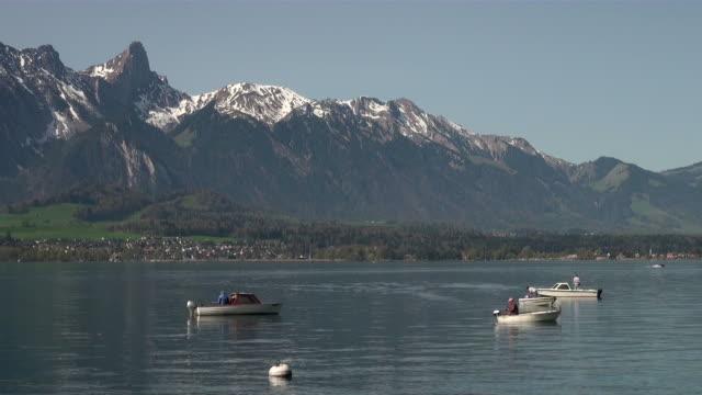 ws boats passing by thun lake  / oberhofen, bernese oberland, switzerlan - berner alpen stock-videos und b-roll-filmmaterial