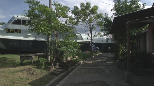 stockvideo's en b-roll-footage met boats rest near homes that washed inland during the 2004 tsunami in banda aceh indonesia - goede staat