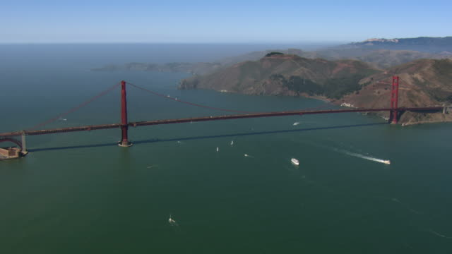 boats sail beneath the golden gate bridge in san francisco bay. - san francisco bay stock videos and b-roll footage