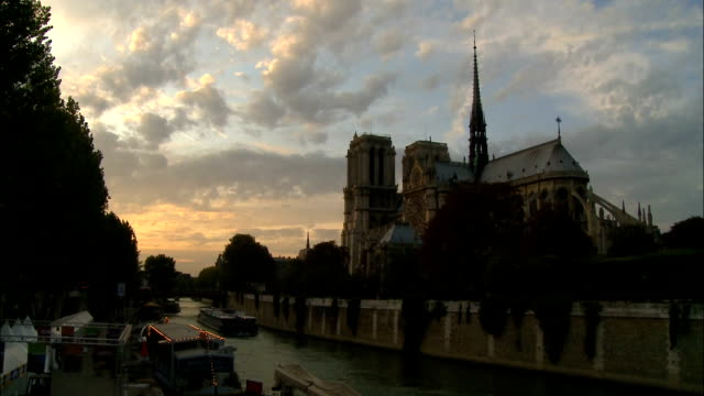 Boats sail on the Seine by the Notre Dame Cathedral in Paris, France.