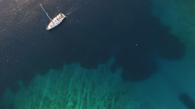 空から見たボートの岩の海岸沿いのセーリング