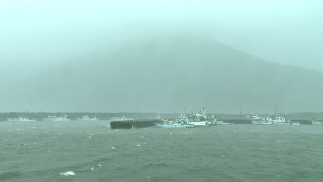 boats tied securely in small fishing port as typhoon noru hits japan - pacific ocean stock videos & royalty-free footage