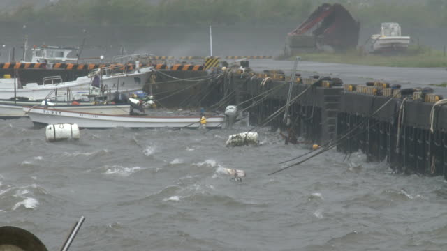 boats tied securely in small fishing port as typhoon noru hits japan - tropical storm stock videos & royalty-free footage