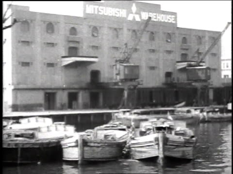 boats tied up at dock with large warehouse behind them / large ship in harbor with tugs moving in foreground / - 1944 stock videos & royalty-free footage