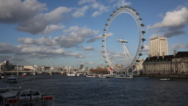 boats travel along the river thames in front of the london eye ferris wheel on february 21, 2014 in london, england. - millennium wheel stock videos & royalty-free footage