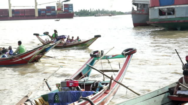 Boats travel in and out of a harbor in Yangon, Myanmar