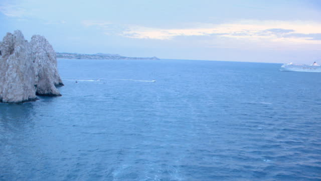 boats travel near the mexican coastline. - cabo san lucas stock videos & royalty-free footage