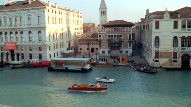 boats travel on the canals of venice, italy. - traghetto video stock e b–roll