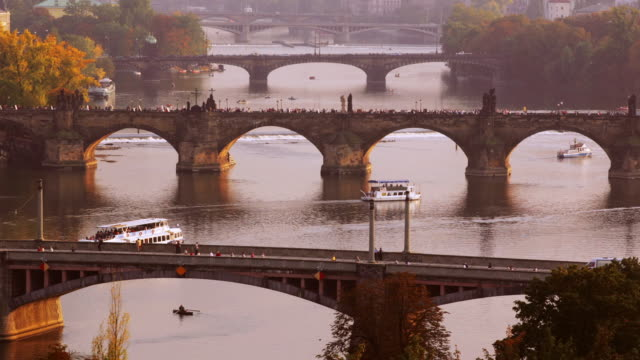 boats travel quickly on the vltava river under prague's jiraskuv bridge and charles bridge. - vltava river stock videos & royalty-free footage
