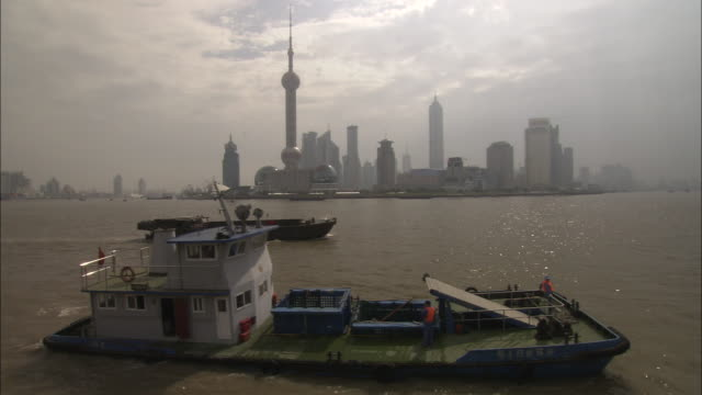 ws boats traveling on river past skyline with oriental pearl tower and jin mao tower / shanghai, china - jin mao tower stock videos & royalty-free footage