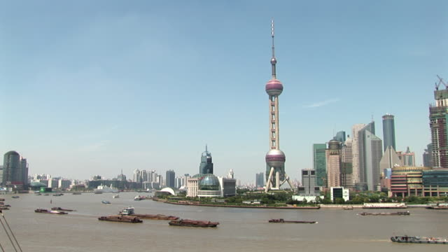 ws boats travelling on huangpu river past pudong skyline / shanghai, china - river huangpu stock videos & royalty-free footage