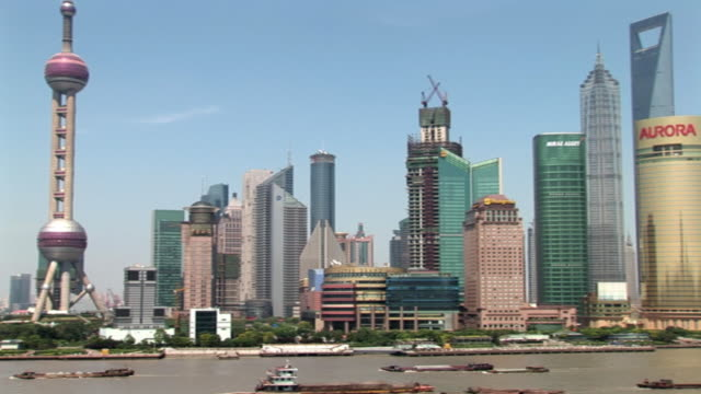ws pan boats travelling on huangpu river past pudong skyline / shanghai, china - river huangpu stock videos & royalty-free footage