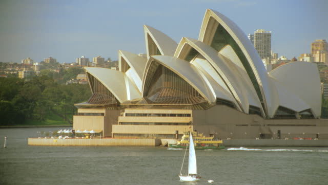Boats travelling through harbor near Sydney Opera House / Sydney, Australia