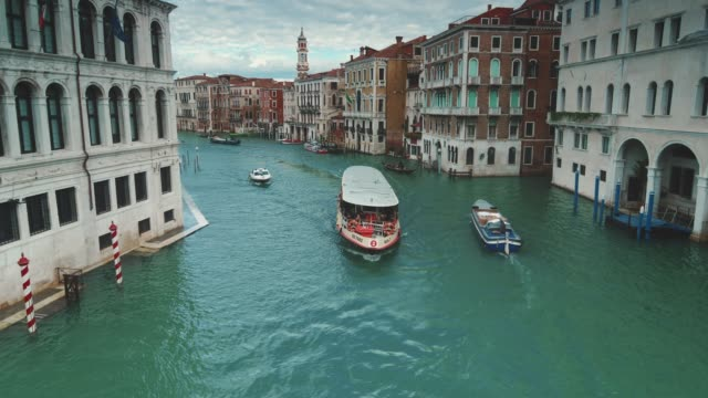 boats traverse the grand canal along amazing city architecture in venice, italy - barca a motore video stock e b–roll