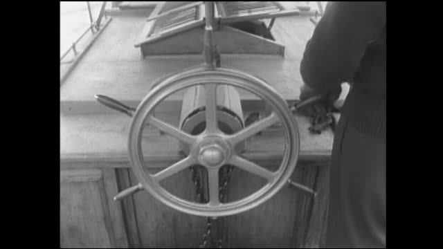 a boatsman handles the helm of a tsukuda ferryboat as passengers and bicycles are towed on the passenger raft. - 舵輪点の映像素材/bロール