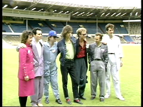 Bob Geldof Midge Ure Elton John Adam Ant Janice Long and Tony Hadley pose for press on pitch at Wemblety Stadium to launch Live Aid