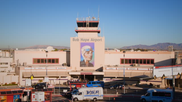 w/s bob hope airport, burbank, with airplane taking off in background: southwest boeing-737 - burbank stock-videos und b-roll-filmmaterial