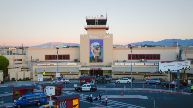 bob hope airport, burbank, with airplane taking off in background: southwest boeing-737 - burbank stock-videos und b-roll-filmmaterial