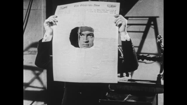 stockvideo's en b-roll-footage met bob hope peers through a hole in a newspaper - gluren