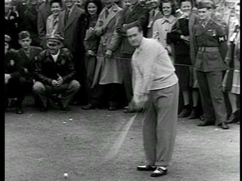 bob hope practicing swing at golf competition raising funds for war bonds / crowd in background - golf shoe stock videos & royalty-free footage