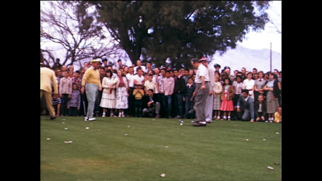 bob hope surrounded by people on the golf course and playing golf; american flag in the background - ボブ ホープ点の映像素材/bロール