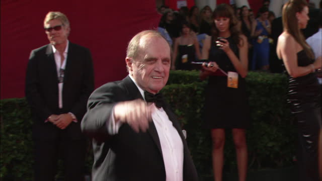 bob newhart waves as he walks on red carpet before making his way over to greet reporter with handshake - ボブ ニューハート点の映像素材/bロール