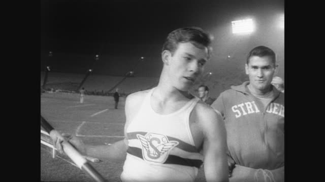 bob seagren after winning coliseum relay title / seagren pole vaults at fresno clearing 17 feet 5 inches setting world record. - スポーツの判定員点の映像素材/bロール