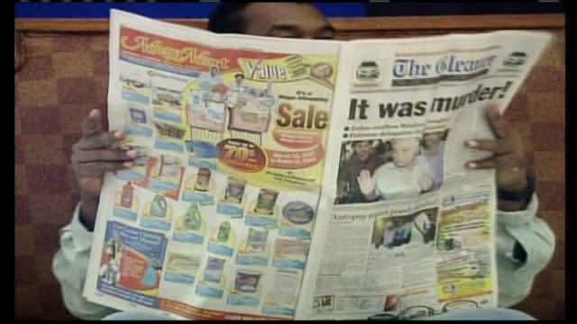 vídeos y material grabado en eventos de stock de possible match-fixing connection; man reading jamaican newspaper with headline , 'it was murder' woman stands amid traffic selling newspapers - jamaiquino