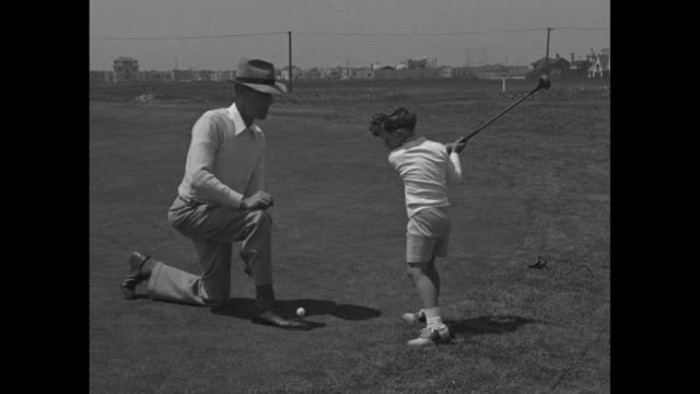 Bobby Dawson and father walk onto green as crowd of children follows / CU Dawson / crowd of children watch / Dawson tees off as father kneels by him...