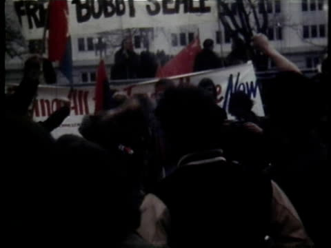 crowd of protesters carrying placards banners flags protester wrapped in american flag / washington dc usa - アメリカ黒人の歴史点の映像素材/bロール