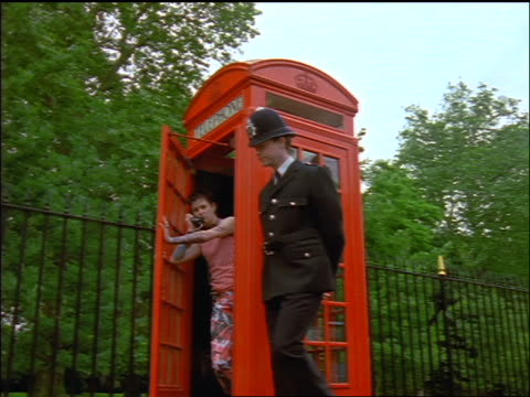 Bobby walking by Generation X man in telephone booth + shakes head / London