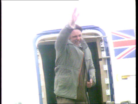 stockvideo's en b-roll-footage met bodies flown home / hostage rescues lib ext freed hostage terry waite from plane and waving - terry waite