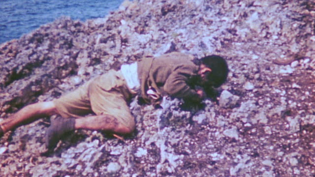 vídeos de stock, filmes e b-roll de bodies of dead japanese civilians at base of cliff from mass suicide during world war ii - apodrecendo