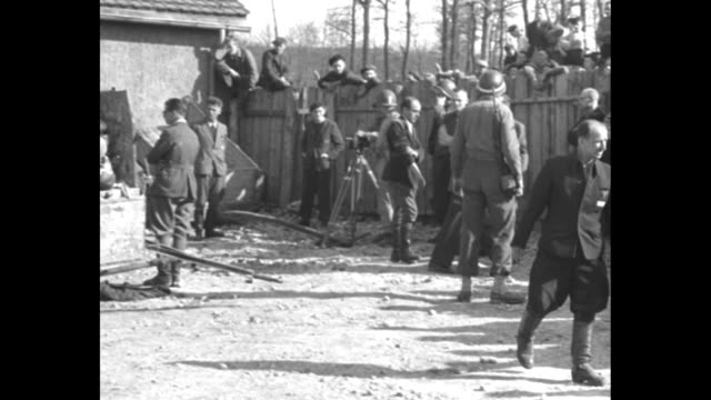 bodies of dead prisoners piled on back of truck in camp pan across to german civilians walking around nearby / pan across group of civilians / bodies... - olocausto video stock e b–roll
