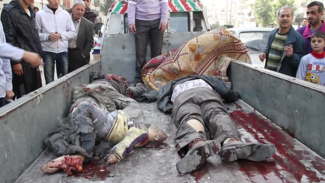 bodies of people killed in a bombing sit in a truck in front of a hospital - cadavere video stock e b–roll