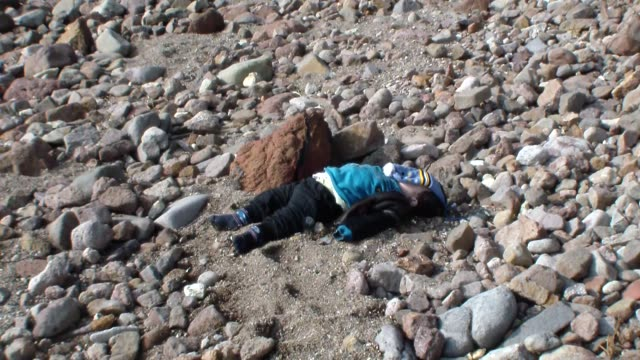 vídeos de stock e filmes b-roll de bodies of refugees are seen on a beach after a boat carrying refugees sank off close to coast of ayvacik district canakkale turkey on january 30 2016... - crise de migrantes europeia 2015 2016