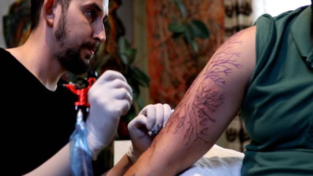 body art at the tattoo studio - giuntura umana video stock e b–roll