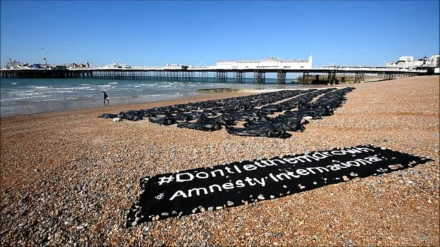body bags lie strewn across brighton beach on englands south coast as part of an amnesty protest against britains shameful response to the... - beach bag stock videos and b-roll footage