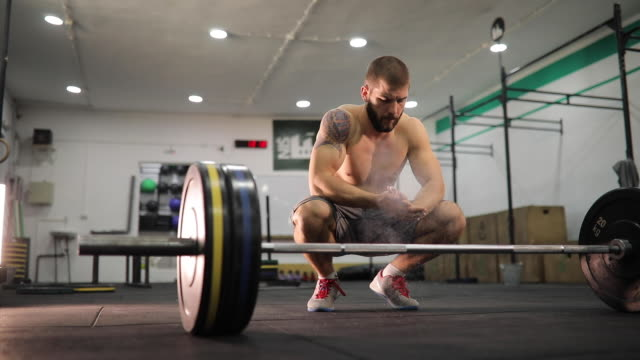 vídeos de stock, filmes e b-roll de construtor do corpo preparando-se para o levantamento de peso - giz equipamento esportivo
