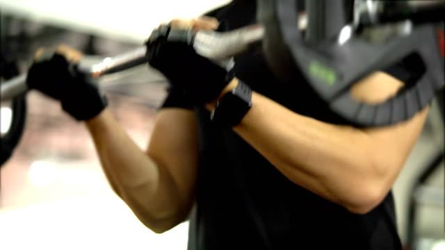 vídeos de stock e filmes b-roll de body builder training biceps with a bar in gym - flexão de braço com peso