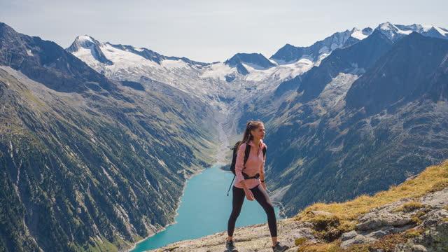 körperbewusste sportlerin wandert im freien in der natur im malerischen berggebiet - berggipfel stock-videos und b-roll-filmmaterial